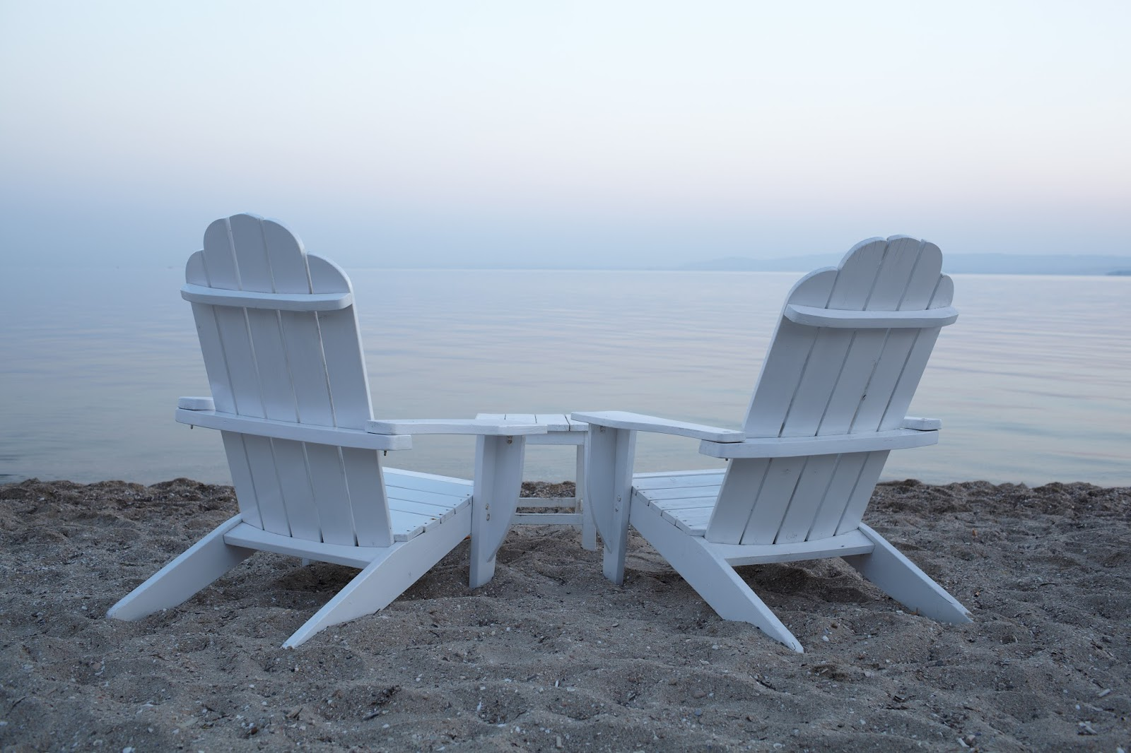 Empty white painted wooden deck chairs on a beach overlooking a calm ocean